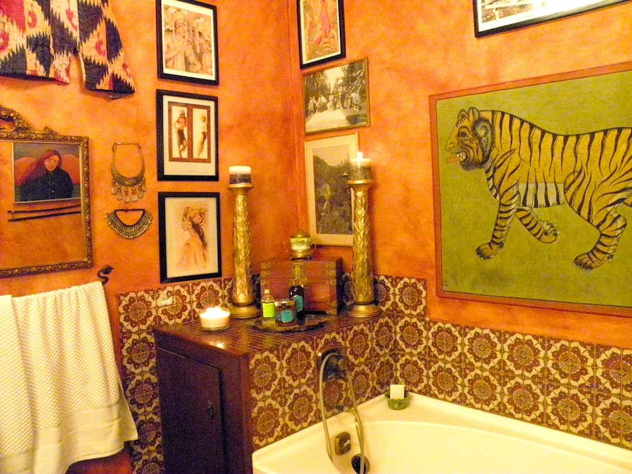 Private bath with luxurious tub, art, and atmosphere with romantic candles