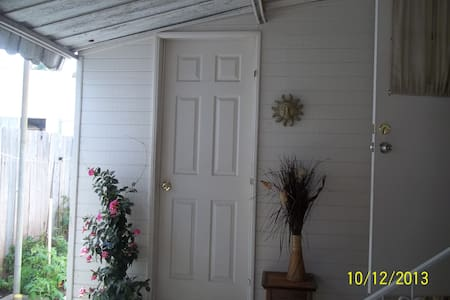Private Guest Room With Private Entrance next to MOBILE HOME with Queen Simmons Beauty Rest Bed, fresh linens, Free  parking,  kitchenette, closet, antique vanity & an enclosed patio.  Close to public transpo. Full use of kitchen & bathroom.
