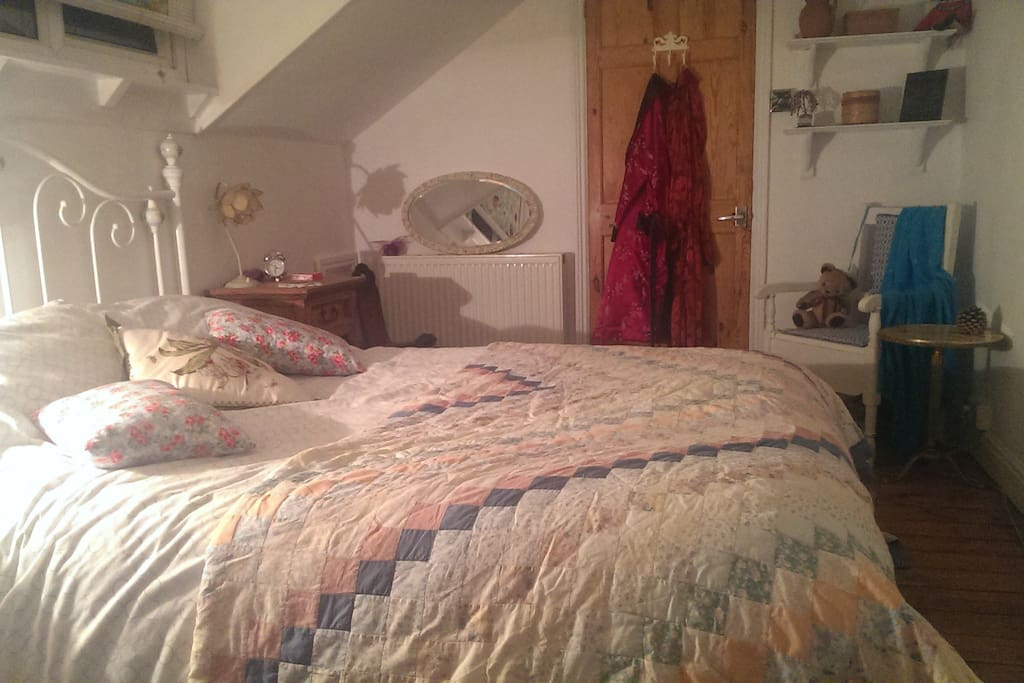 An extremely comfortable bed in a bright and clean attic room.