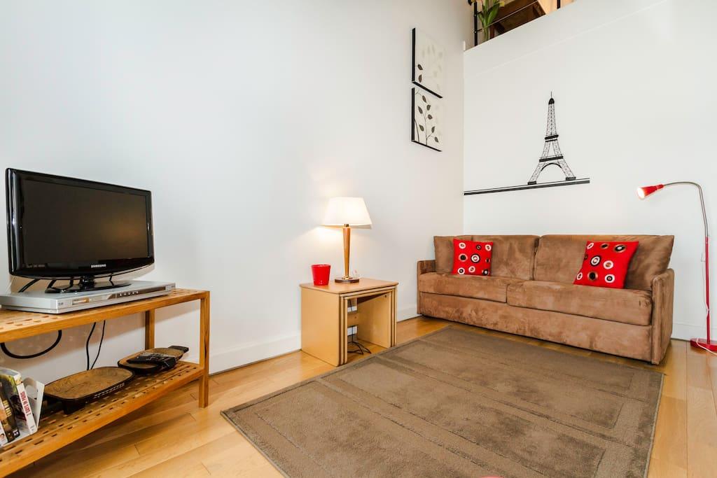 Le salon avec le canapé et la télévision