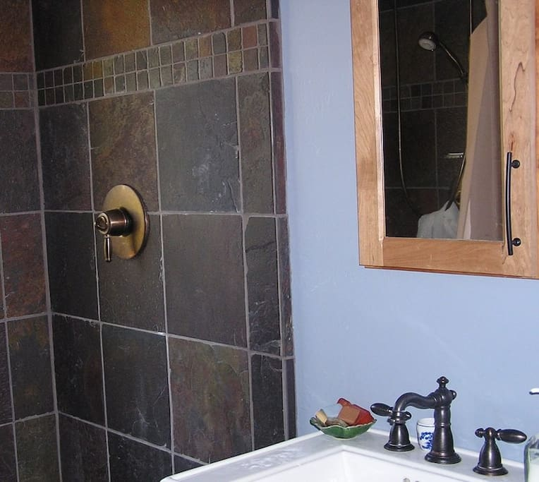 Two person , slate walk in shower with casement window to the Japanese Garden.