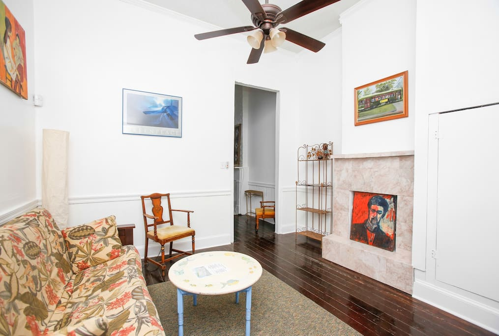 Just off the bedroom is the living room with a futon and beautiful wood floors and closet