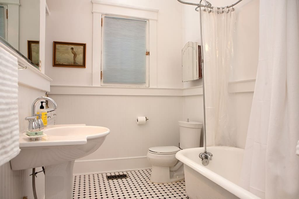 Downstairs bathroom with original, newly restored claw-foot tub, shower