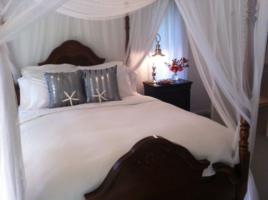 Romantic queen canopy bed made with freshly pressed luxurious linens