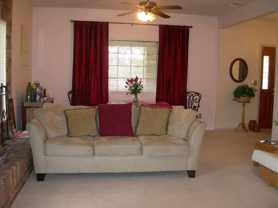 Another Living room couch with dining room table & chairs, with a large  behind it.