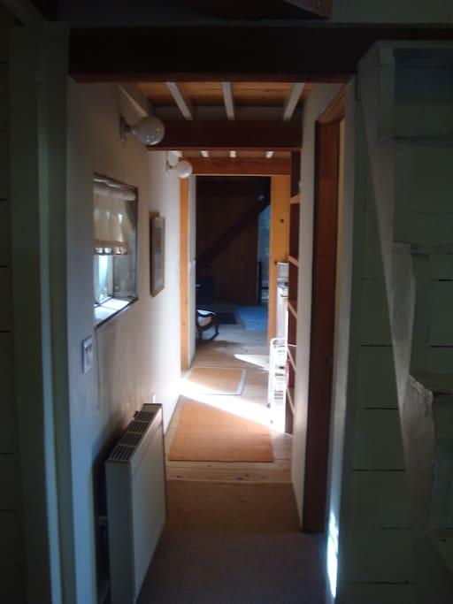 Hallway corridor from BR looking to LR. Loft staircase on right. Propane wall heater on left