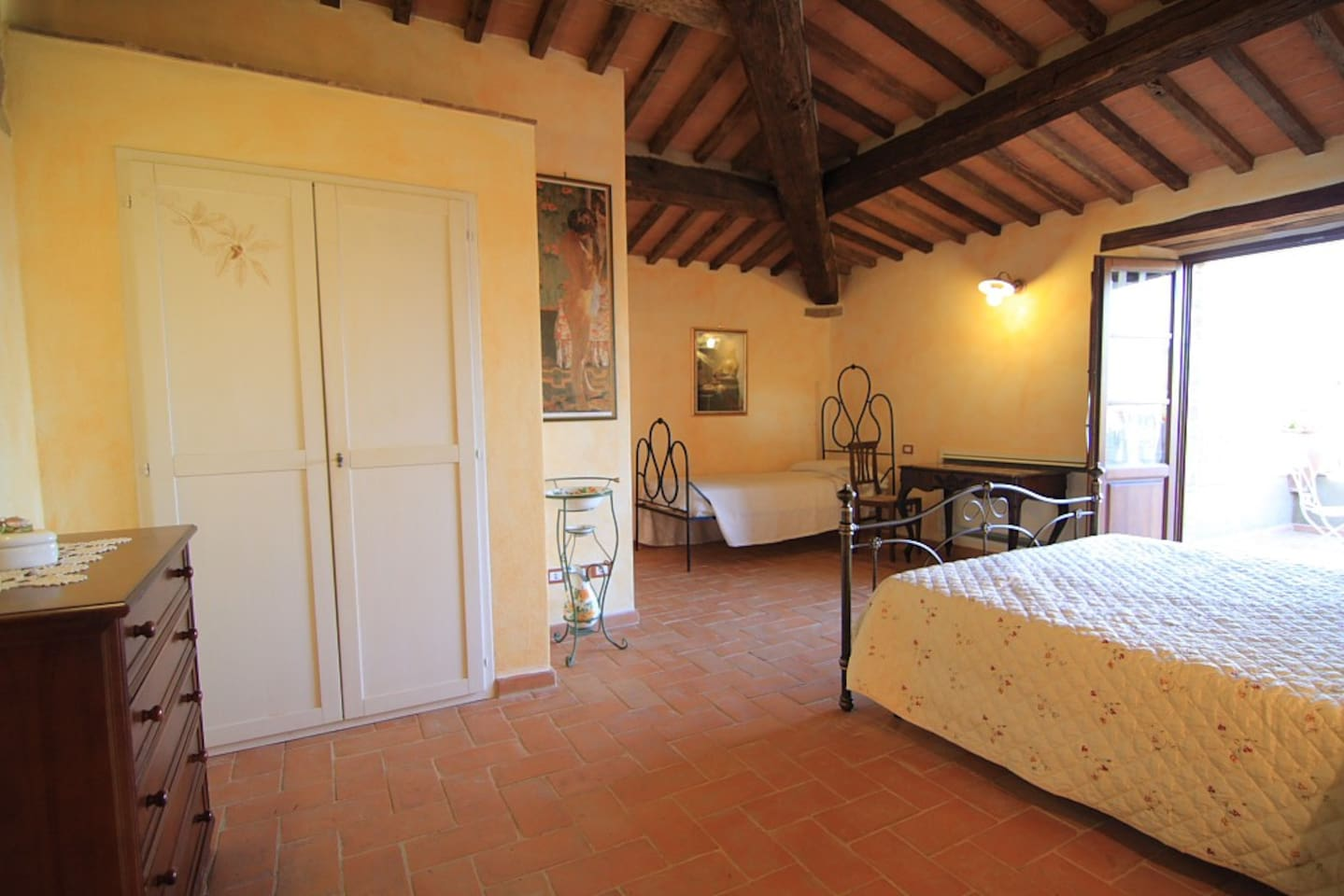 Bedroom on the first floor, with one king size bed and a single bed. Exit to the panoramic terrace