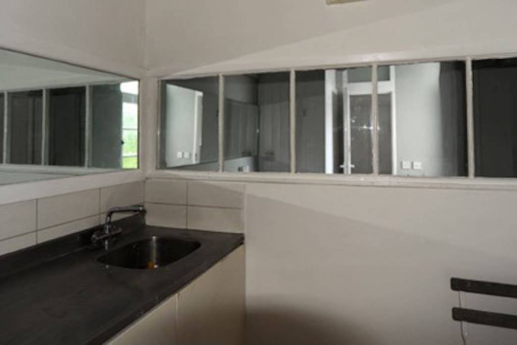 Kitchen and hall mirrors with bathroom beyond