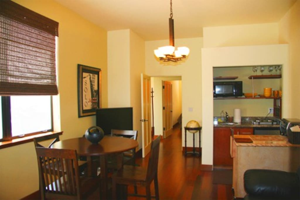 Kitchenette, table chairs, and extra large flatscreen TV. View to the colorful gardens