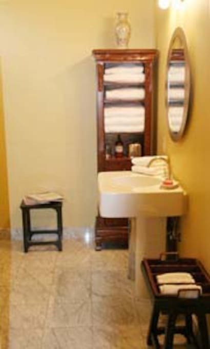 Marble bathroom, walk in shower with pull down cedar seat, shampoo, conditioner, soap, fluffy cotton towels