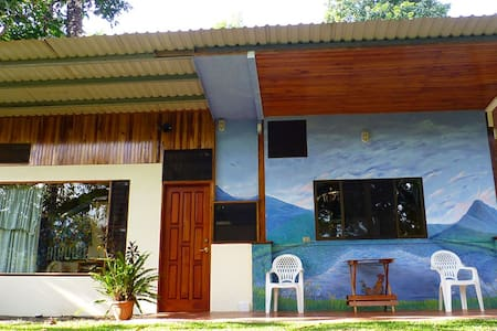 An artistic secluded cabin in the middle of lush gardens and dense forests — yet just 2 kilometers to Nuevo Arenal. HiSpeed WiFi. Great kitchen. Awesome bathroom. Daydream patio. Studio cabin — extra bedroom attached. Sunny Cheerful Secure.