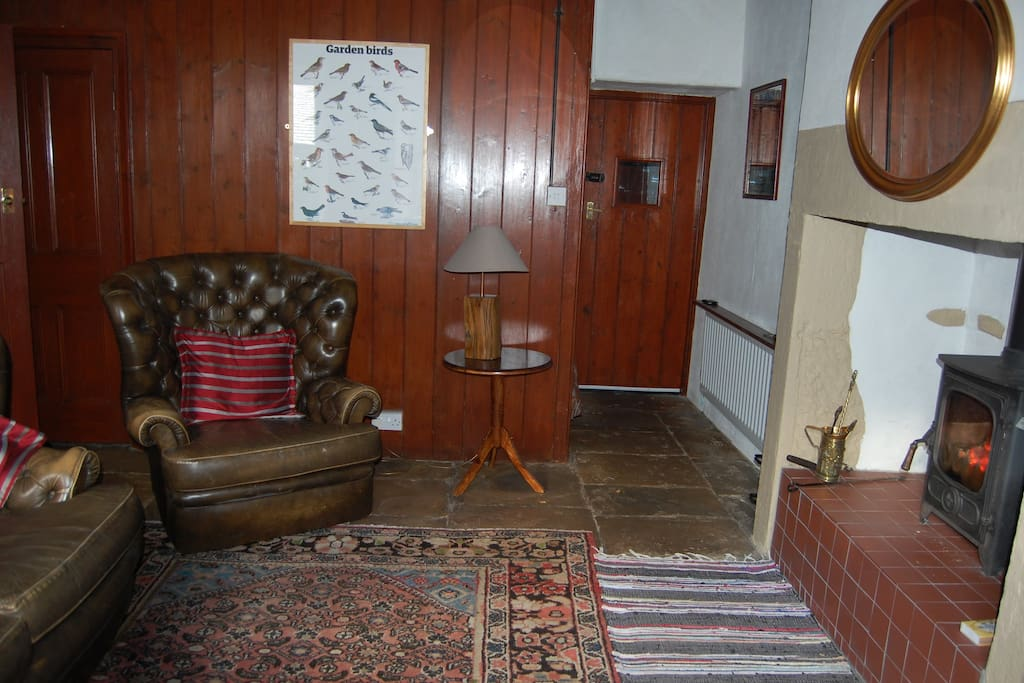 Spacious lounge, with stove and original wood panelling