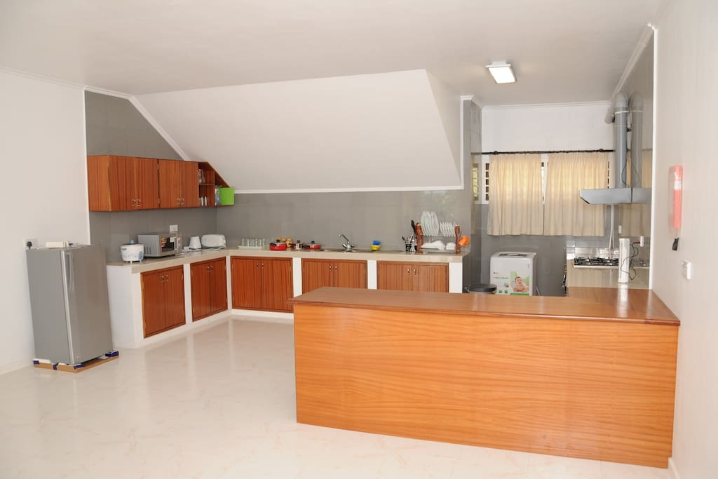Large open kitchen fully equipped with fridge, microwave, oven, rice cooker, kettle, cutlery and washing machine.