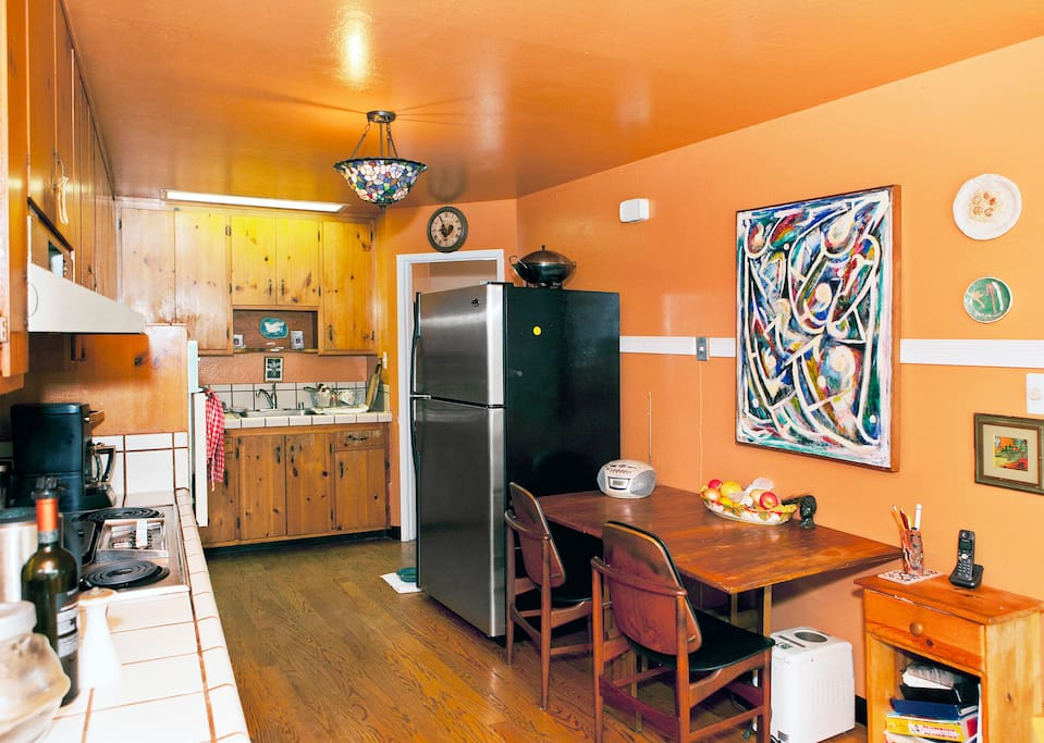 Spacious kitchen area with large refrigerator, coffee maker, four burners on stove, oven and microwave and plenty of pots, pans, plates, cups and bowls. All that you need!