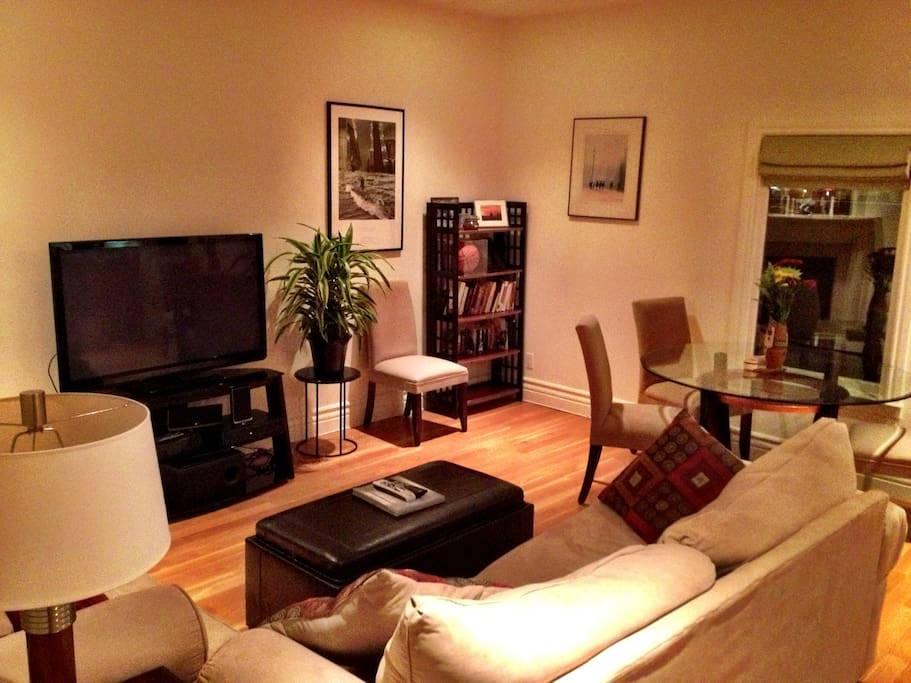 "Spacious living room with 50"" TV, comfy couch, dining table for four and gas fireplace"