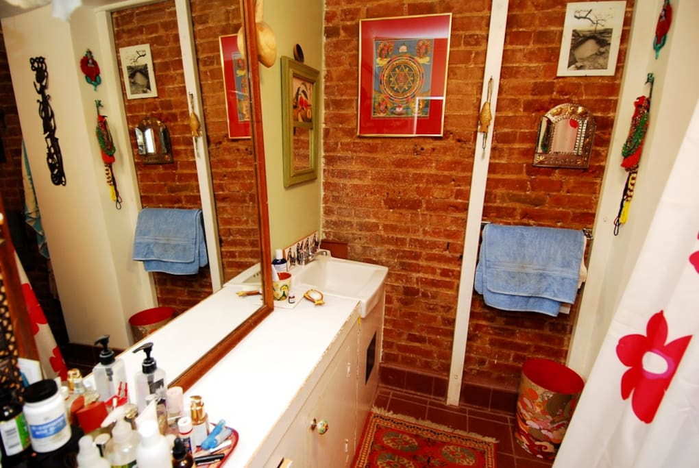 Large bathroom with brick walls and delicious old fashioned bathtub