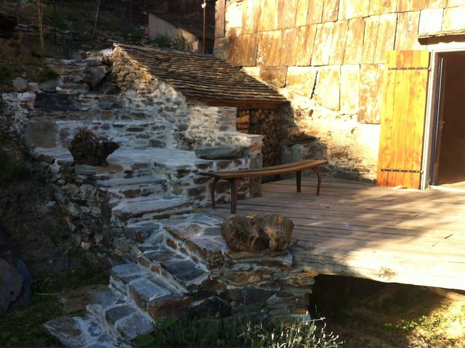 Terrasse, barbecue et réserve de bois.