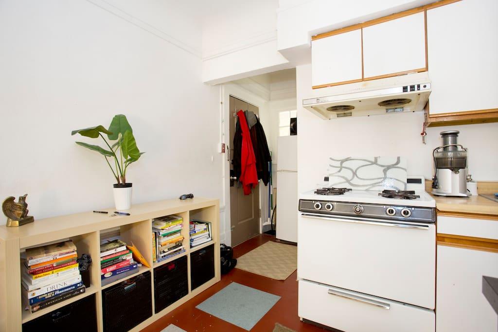 The bathroom door is behind the stove
