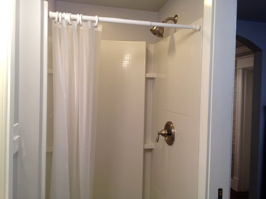 The shower has multiple shelves, with toiletries and extra towels available in the bath cabinet.