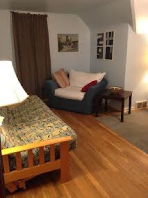 futon/double bed, tv and comfy chair in sitting area