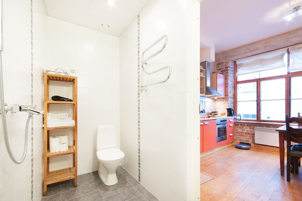 Toilet, shower, sink, washer are in same room. Shower is open, without curtain.