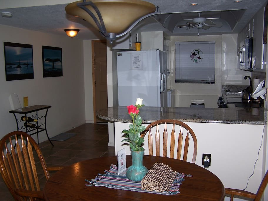 Fully equipped kitchen has granite counters, glass top stove, microwave, dishwasher and dining area. View of launches from kitchen window