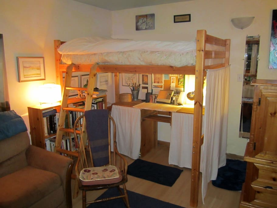 Queen size loft bed with goose down duvets, desk, & books.
