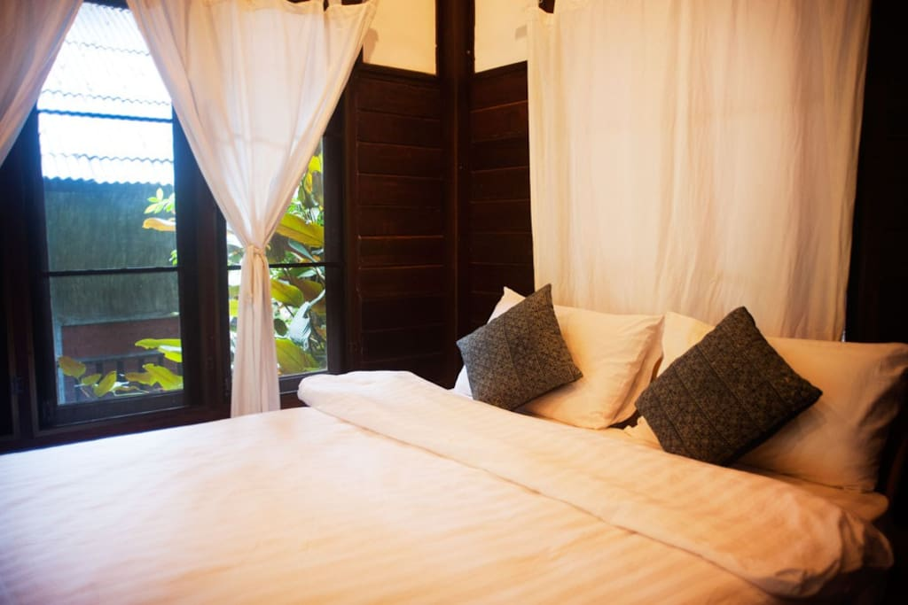 this room has a river view balcony and a cozy queen sized bed