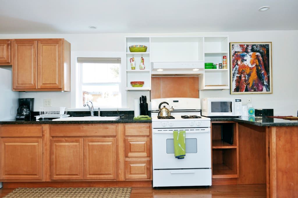 Full kitchen with stove, microwave, toaster, electric tea-pot, double sink and granite counters.