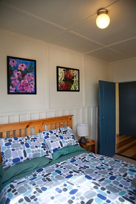 Double bed with electric blankets, bedside tables made from recycled timber, original acrlics featuring tasmanian flora.