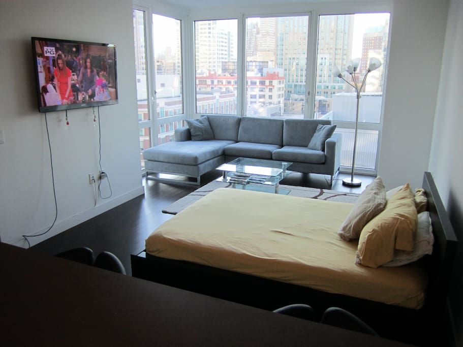 Full-Sized Bed, Flat-Screen TV, and Sofa with Coffee Table