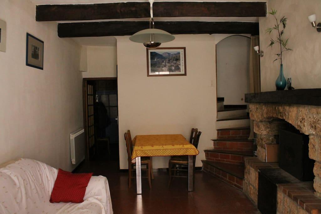 Salon salle à manger. Porte à gauche donnant sur la cuisine. Escalier menant aux chambres