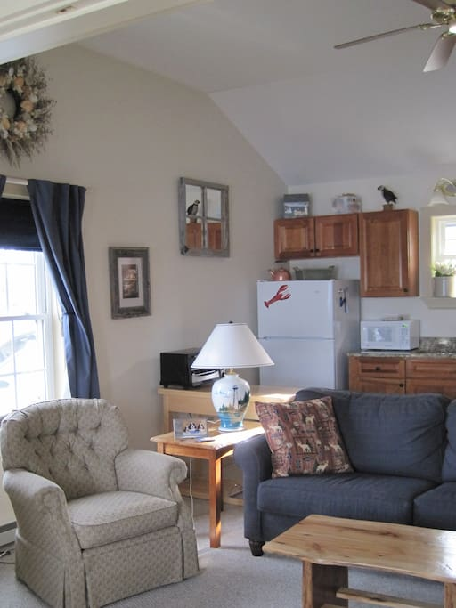 Living area showing sleeper couch & kitchen with toaster, microwave, coffee maker and dishes for your stay.