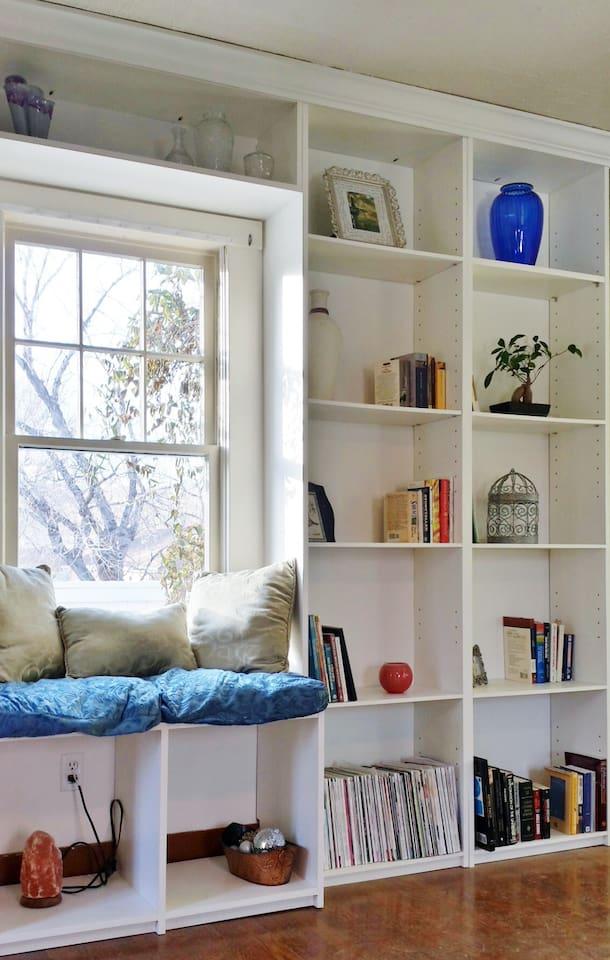 The window seat in the living room is a great place to read a book.