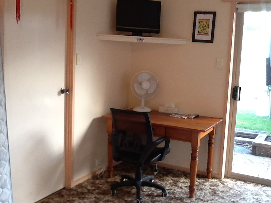 The bedroom has a television, desk and fan.