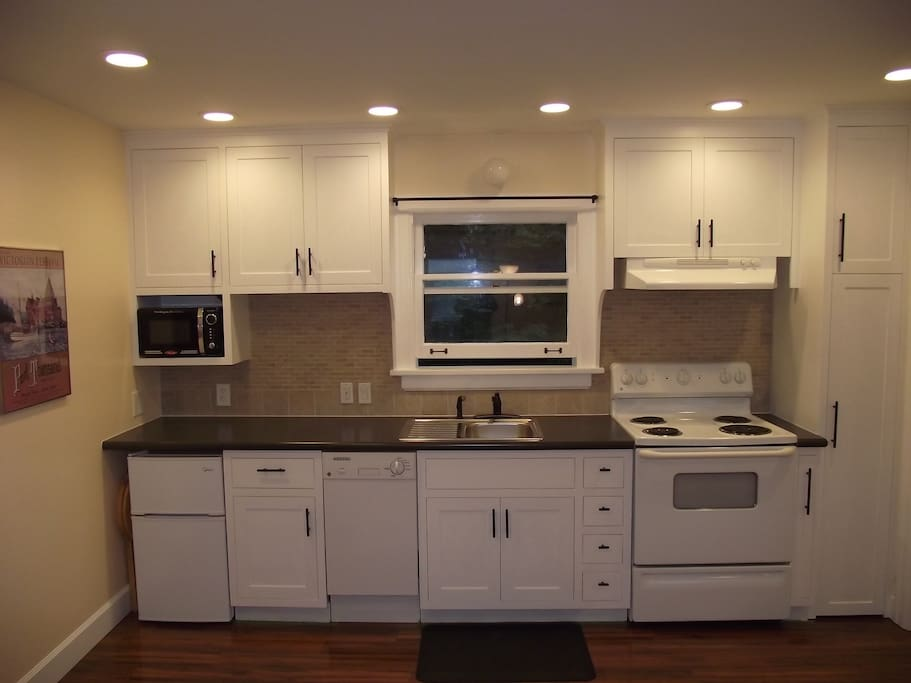 Full Kitchen with dishwasher, stove, microwave and smaller fridge