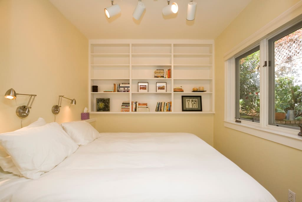 Cozy king-size bed peeks into the garden; features pure cotton bedding, reading lights and small library.