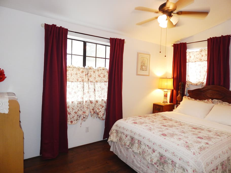 Second bedroom has a queen bed, wood floors, vaulted ceilings, ceiling fan, dresser & black out curtain.