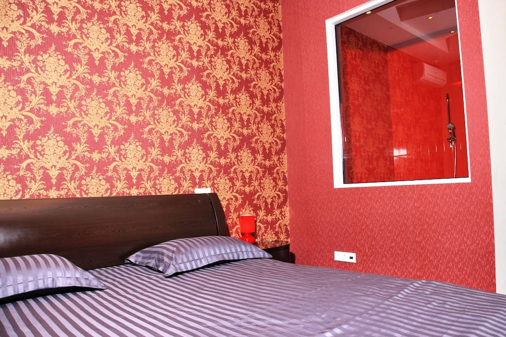 Bedroom King-size bed with all cotton sheets. Has spectacular view over  Khreshchatyk street. Due to author`s designe this room has window to 1st bathroom.