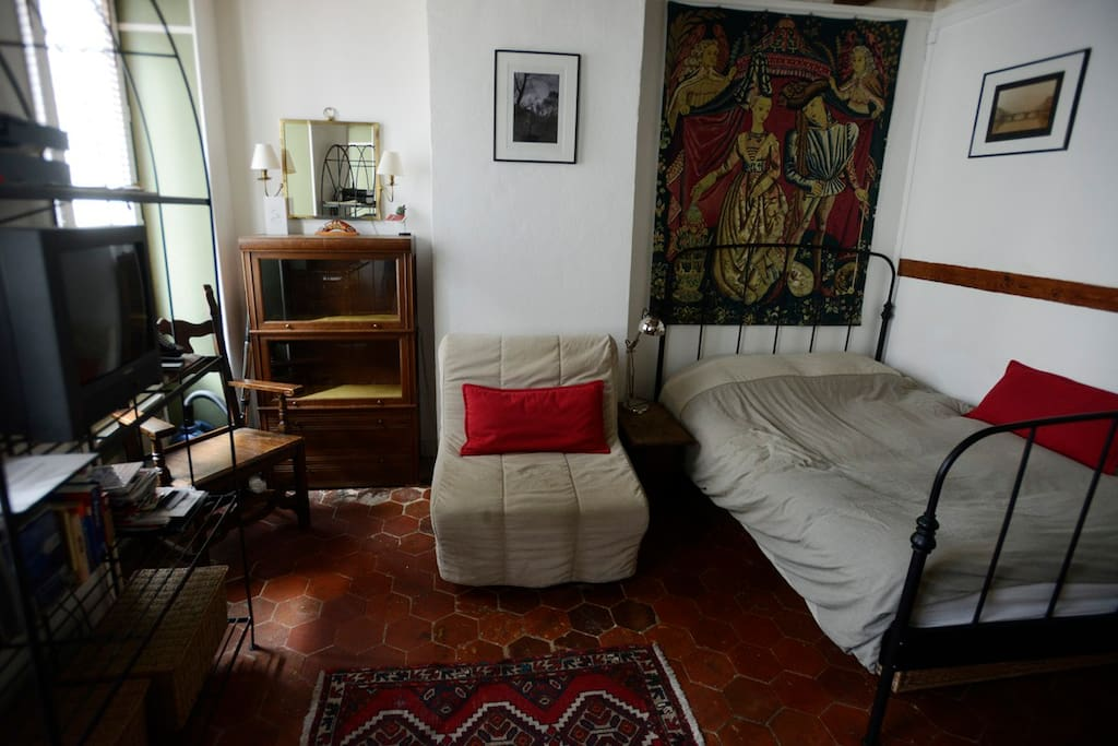 The main room of the studio with new double bed, single pull-out bed and decorated with antique furniture and original photography.
