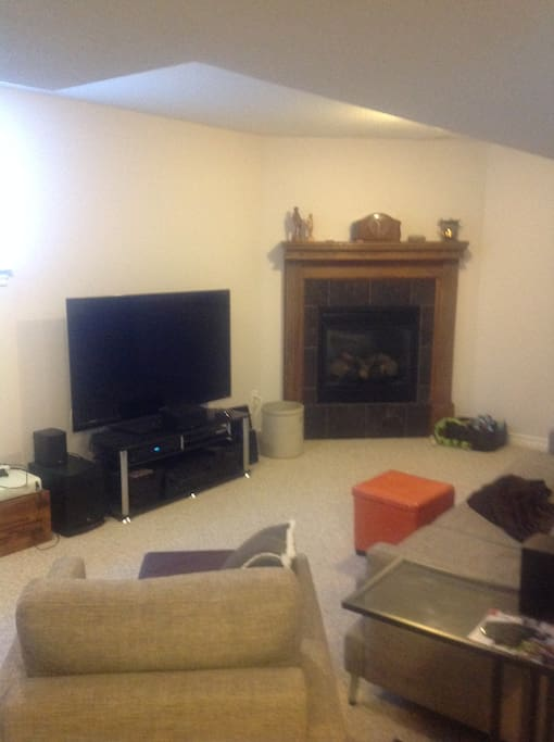 Bright, spacious sitting room with gas fireplace and big screen TV.