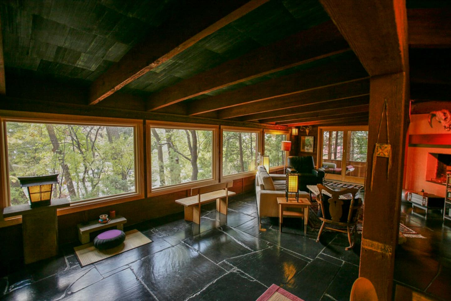 Living room, with black slate floors, looking over gardens and wall of trees. Complete privacy in an urban setting.