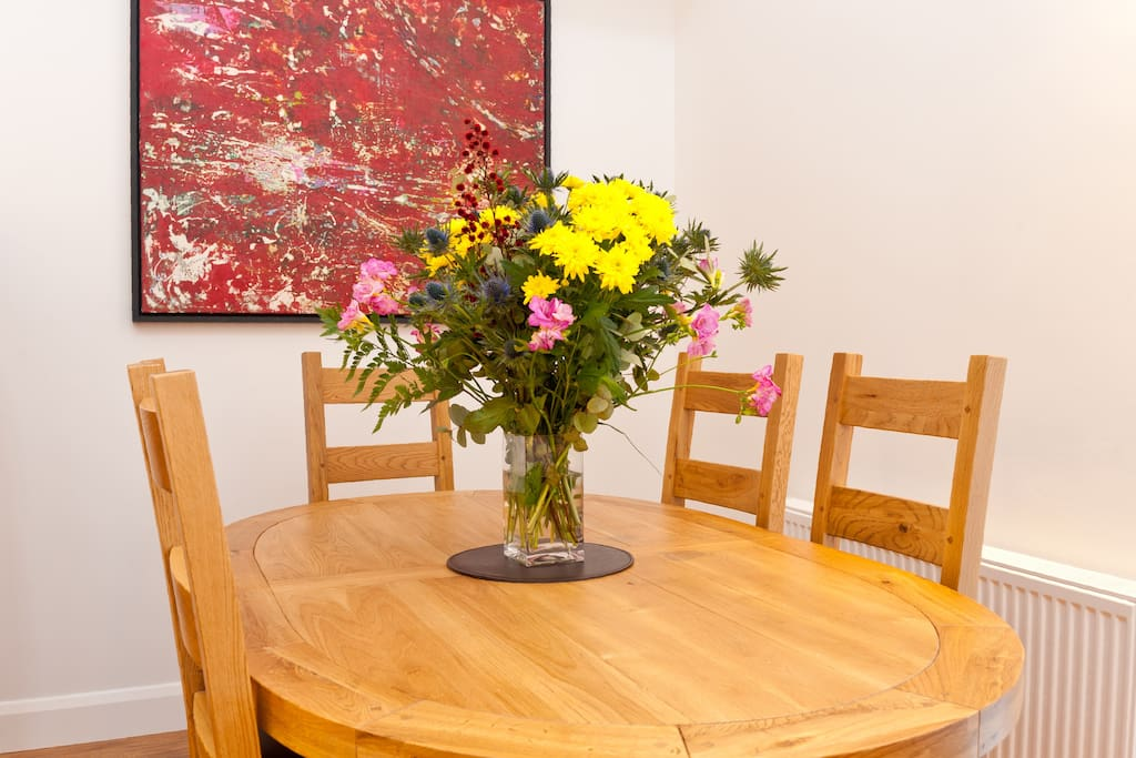 The dining table is a beautiful hardwood table that is surrounded by six comfortable chairs.