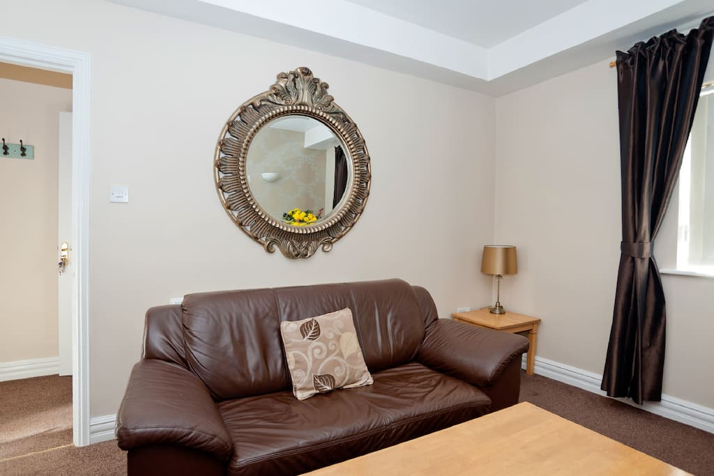 The gold mirror above the leather sofa bed in the sitting room.