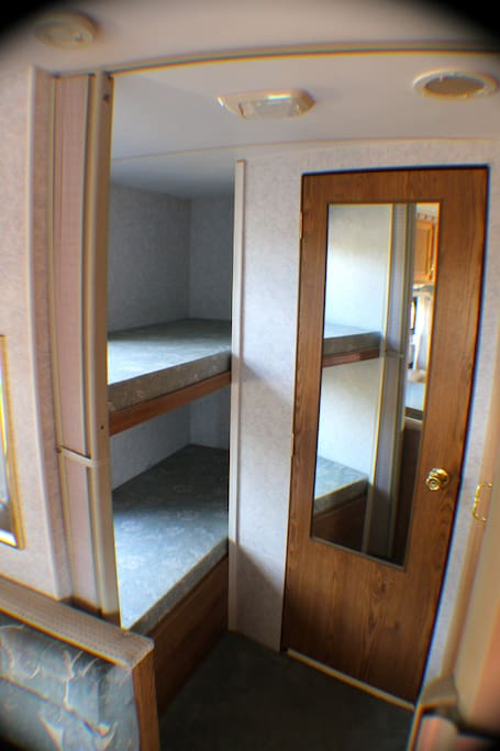 Bunk beds for the kids with their own insulated privacy blinds.