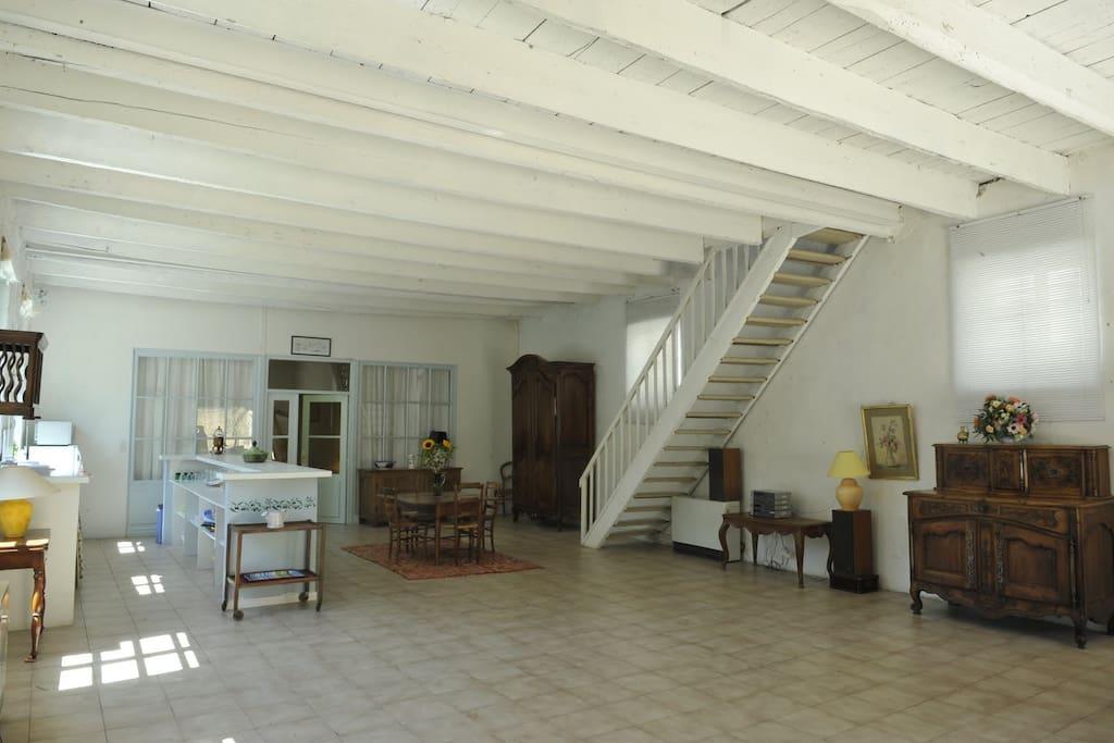 Une vue de la vaste salle-de-séjour avec escalier qui mène à l'étage au-dessus.