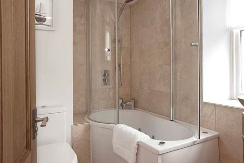 Luxury bathroom with shower above a spa bath. Waterfall tap, Villeroy and Bosch fittings.