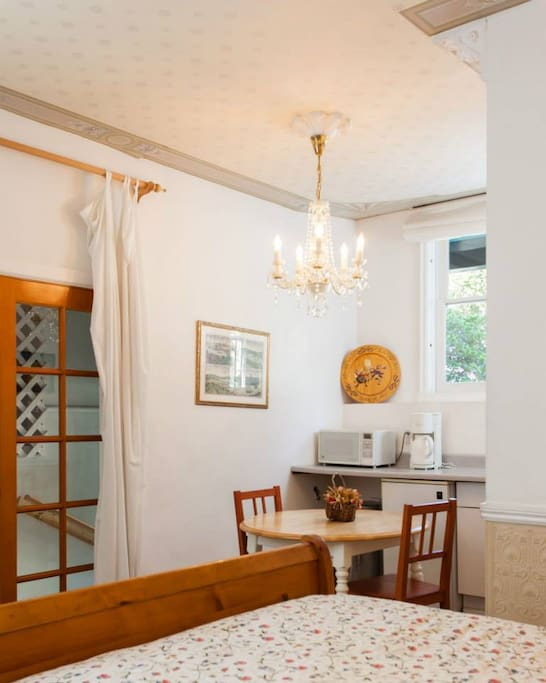 The ground floor unit with private entrance, private full travertine marble bath, (shower), queen bed, and kitchenette (microwave, coffeemaker, fridge). The unit has two windows, one looking out onto the tree- lined street in the front of the building.