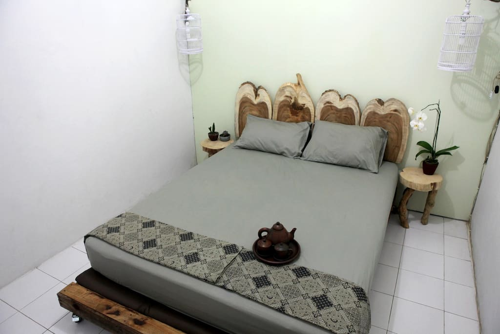 Kamar Nasi, we made the bed and side tables by hand. The room is equipped with a fan, has a desk, chair and wooden clothes rail. Enjoy the shadows from the birdcage lamps.