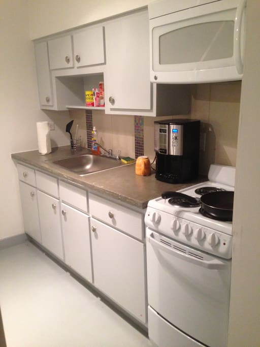 Kitchen includes refrigerator, microwave, coffee-maker, oven and stove. i